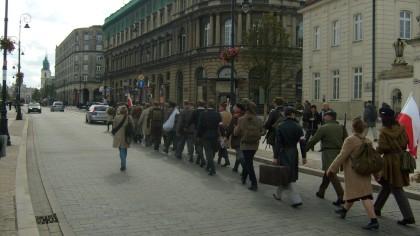 Maszerujący na tle Hotelu Europejskiego w Warszawie