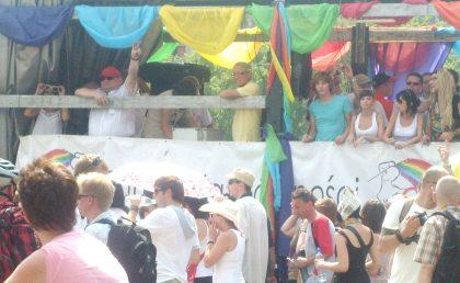 Poseł Kalisz w czerwonej czapeczce pozdrawia z platformy na paradzie