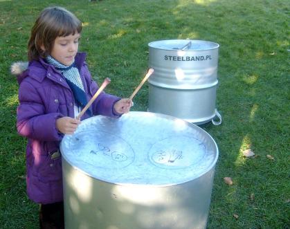 Dziewczynka gra na metalowym bębnie Park Bródnowski