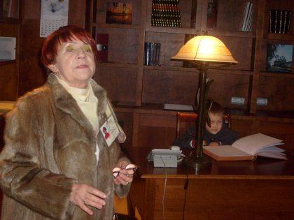 Przewodniczka turystyczna opowiada o historii w bibliotece dworku